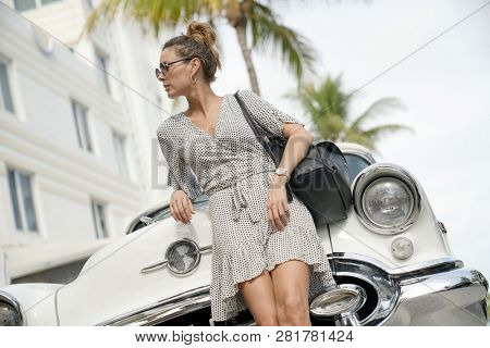 Stunning stylish young woman standing infront of vintage car
