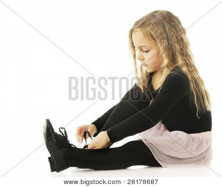 An adorable kindergartner putting on her tap shoes.  On a white background.