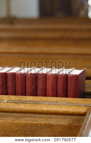 Detail Of A Church Interior, A Row Of Red Hymn Books On A Church Pew. Depicts Religion And Prayer