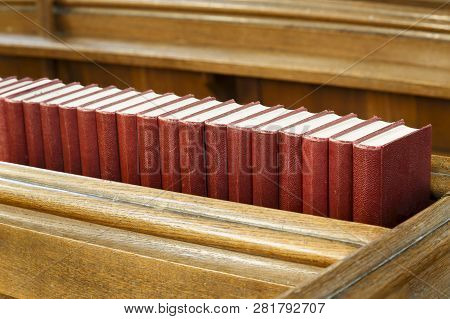 Closeup Of A Row Of Red Hymn Books On An Old Wooden Church Pew. Depicts Religion And Prayer