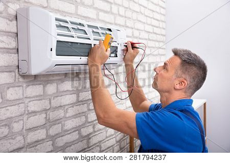 Male Electrician Checking Air Conditioner With Digital Multimeter