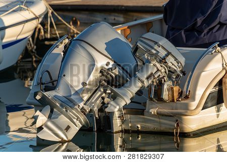 Detail Of Two Outboard Motors (engines), On A Boat Moored In The Port With Reflections