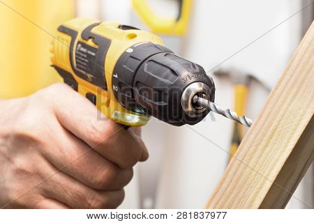 The Drill Drills Into The Wood. Drill In Hand