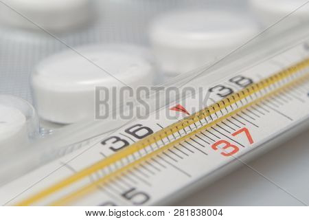 Medical Thermometer And Pills On White Background. Medicines And Medical Thermometer