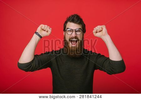 Hnadsome Excited Bearded Manin Glasses Is Celebrating Victory
