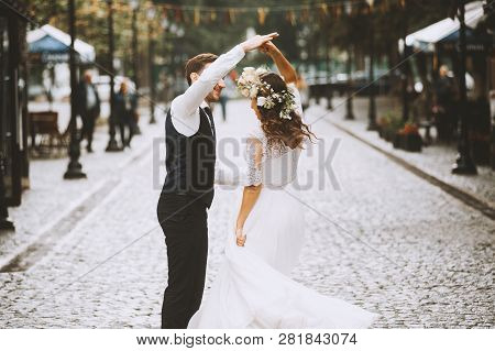 Newlywed Couple Dancing In The Street, Happy Emotional Bride Dancing Outdoors With Elegant Groom