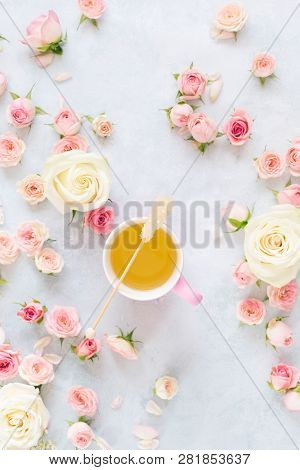 Tea Cup With Roses. Flat Lay Of Rose Flowers , Petals And Cup Of Tea Over Textured Background