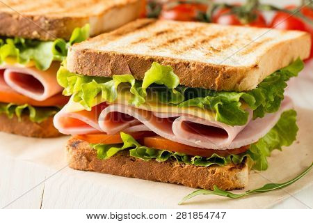 Close-up Photo Of A Club Sandwich. Sandwich With Meat, Prosciutto, Salami, Salad, Vegetables, Lettuc