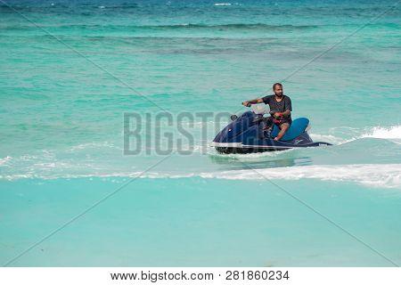 Maafushi, Maldives - 9 Dec 2018: Maldivian On A Jetski. Man On A Water Scooter Makes A Turn. Pure Bl