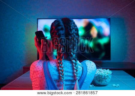 A Young Girl Watching Movies With A Remote Control With A Bowl Of Popcorn On The Background Of The T