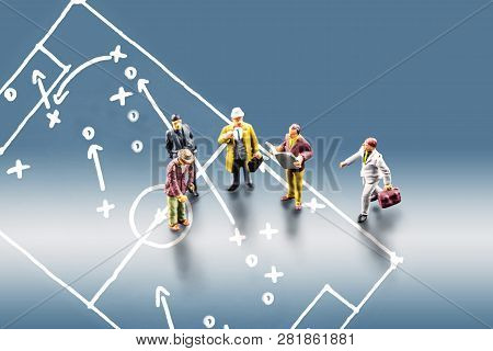 Group Of Miniature Business Men Figurines Standing Together And Leading A Discussion With The Pictur
