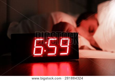 Rectangular Alarm Clock On The Bedside Table With Red Numbers, Sleeping Man In Bed In Dark Room. Con