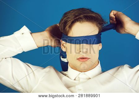 Blindfolded Man With Tie On Eyes In White Shirt On Blue Studio Background, Fantasy And Bdsm, Dishone