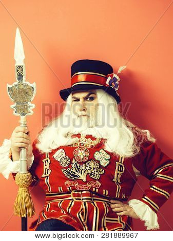 Frown Senior Man Beefeater Yeomen Warder Or Male Royal Guard Bodyguard In Uniform With Spear On Red