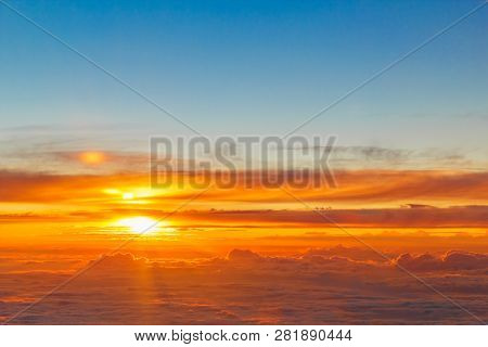 Beautiful Golden Sunset over Clouds. Bright Sunshine through Clouds with Blue Sky Above.