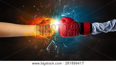 Two hands fighting and breaking glass into small pieces with fire and water concept
