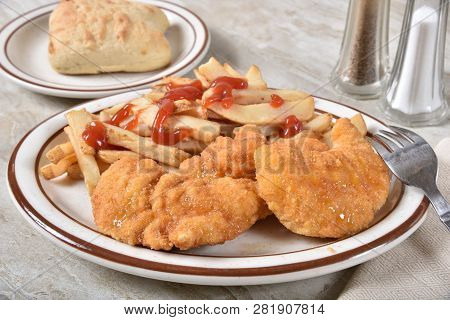 Breaded Fried Chicken Breast With French Fries And Catsup