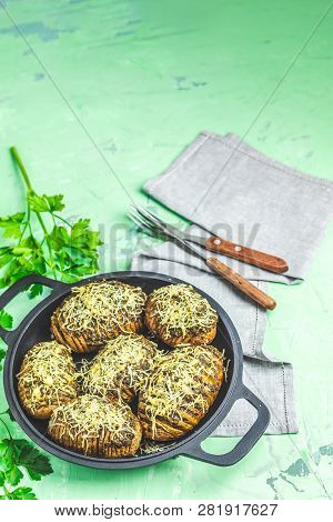 Delicious Portion Baked Potatoes In Black Frying Pan With Pesto Sauce
