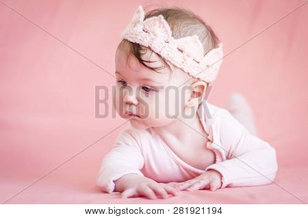 Sweet Adorable Six Months Old Caucasian Baby Girl With A Pink Cloth Crown On A Pink Background. Infa