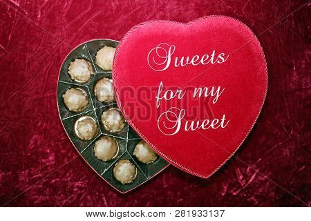 Valentines Day. Red Velvet Heart Shaped Valentines Day Chocolates Box. On Burgundy Red Velvet background.  Text reads, Sweets for my Sweet