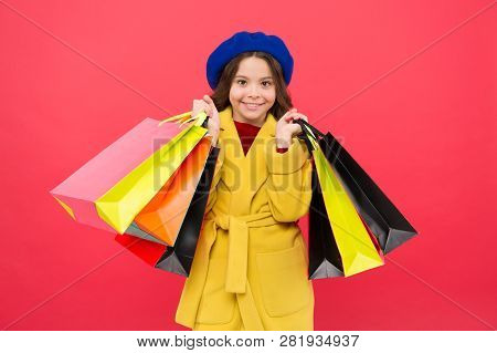 Girl Cute Kid Hold Shopping Bags Red Background. Get Discount Shopping On Birthday Holiday. Fashioni
