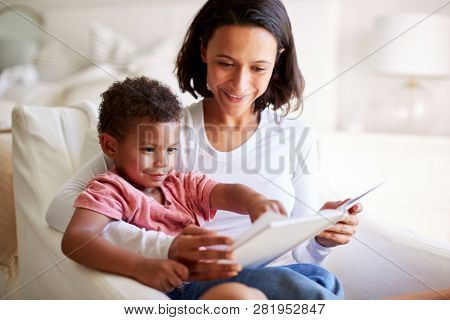 Close up of mixed race young adult mother sitting in an armchair reading a book with her three year old son on her knee, close up poster