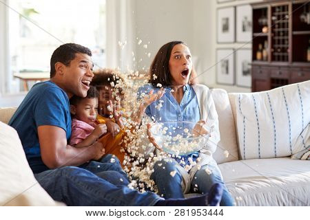 Young mixed race family sitting together on the sofa in their living room watching a scary movie accidentally throwing popcorn in the air