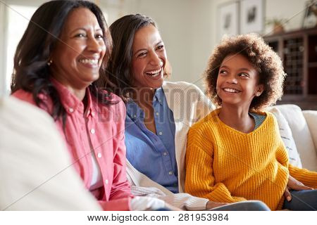 Three generation family female family group sitting on a sofa in the living room watching TV and laughing, selective focus