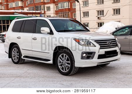 Novosibirsk, Russia - 01.30.19: Used Lexus Lx570 2013 Year White Pearl Color With Headlights On Stan