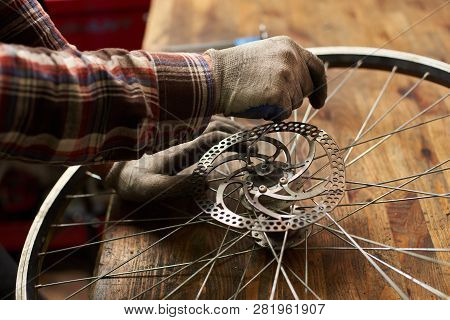 Cropped View Of Male Mechanic Working In Bicycle Repair Shop, Serviceman Repairing Bike Wheel Using