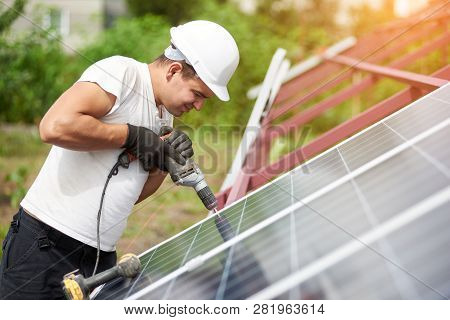 Profile view of technician connecting blue shiny solar photo voltaic panel to metal platform using electrical screwdriver on warm summer day. Stand-alone solar panel system installation concept. poster