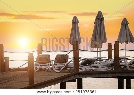 Stunning View Of Closed Umbrellas And Chairs Being On The Wooden Pier At Beautiful Sunset. Sky Is Re