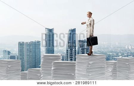 Confident Business Woman In Suit Standing On Pile Of Documents And Looking At Watch With Cityscape O