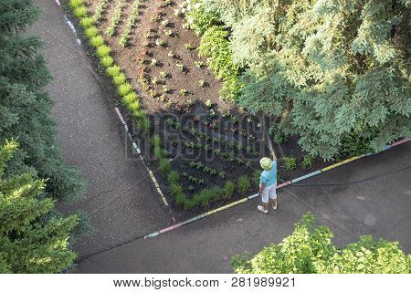 Unknown Man Watering A Flower Garden With A Hose . The View From The Top.