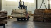 Shop for the production of plywood.The loader carries a stack of plywood. Business wood processing. Woodworking industry. poster