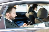 Side view of mid adult CEO using mobile phone while traveling with bodyguards in car poster