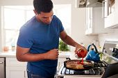 Young adult black man standing in the kitchen cooking on the hob, adding a sauce to the frying pan, close up poster