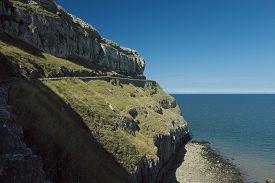 Rocky Cliffs With Narrow Road Overlooking The Irish Sea At Llandudno (wales, Uk) Against A Deep Blue