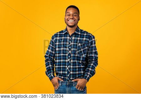 Black Millennial Guy Smiling To Camera Standing Holding Hands In Pockets Posing Over Yellow Backgrou