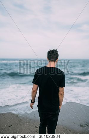 Smiling Guy In A Black T-shirt Stands On The Sandy Seashore.