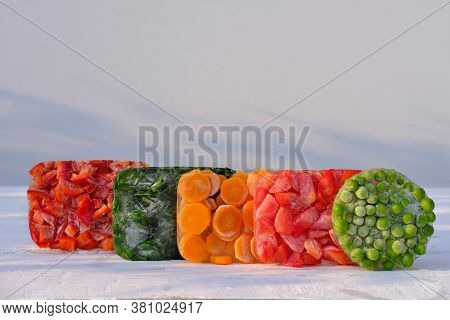 Frozen Vegetables On Wooden Table. Harvesting And Preserving Vitamin Veggies For Winter. Frozen Carr