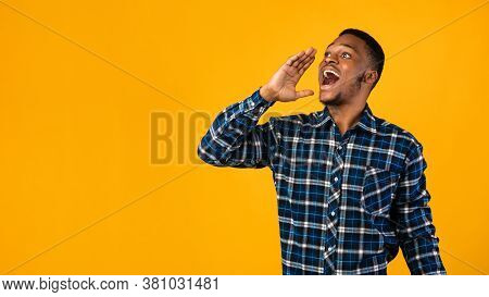 Hey, Attention. Positive Black Man Shouting Holding Hand Near Mouth Advertising Something Standing O