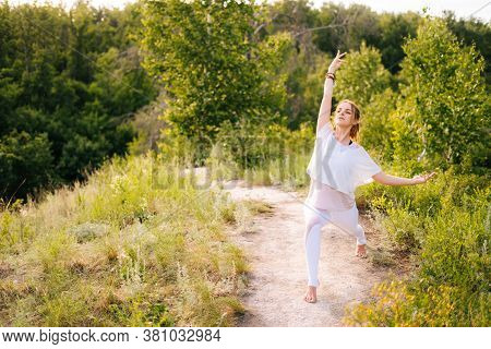Caucasian Young Woman Is Practicing Yoga On Park Outside The City. Meditative Lady With Flexible Bod