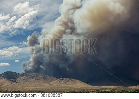 Blue And White Sky Puffy Cumulonimbus Clouds And Smoke From A Large Wildfire In The Desert