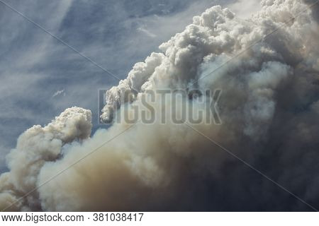 Blue And White Sky Puffy Cumulonimbus Clouds And Smoke From A Large Wildfire