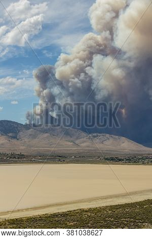 Blue And White Sky Puffy Cumulonimbus Clouds And Smoke From A Large Wildfire In The Desert Muddy Lak