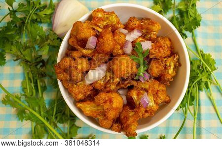 Cauliflower Florets Cut, Spiced And Fried. Gobi Oil Fried With Onion Pieces.