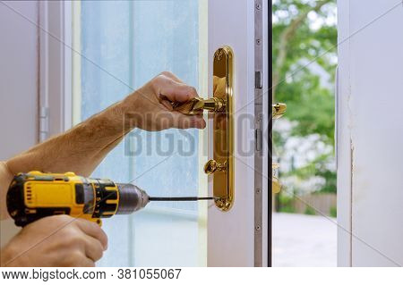 Professional Locksmith Installing Or New Lock On A House Door Handle With Screwdriver