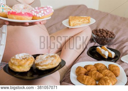 Close Up Of Hungry Pregnant Woman Sitting On The Bed Is Eating A Lot Of Unhealthy Food Such As Crois