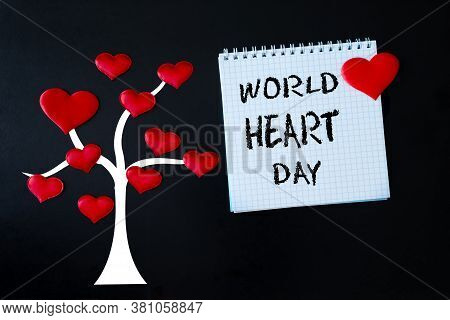Red Hearts On The Image Of A Tree And A White Sheet Of Notepad With The Inscription World Heart Day.